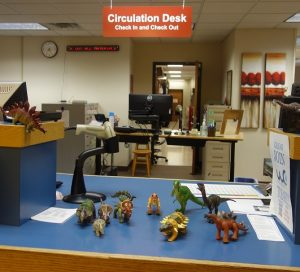 toy dinosaurs on the Library circulation desk